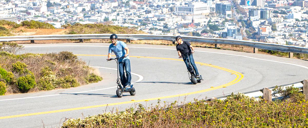 Two people riding their scooters on a mountain road