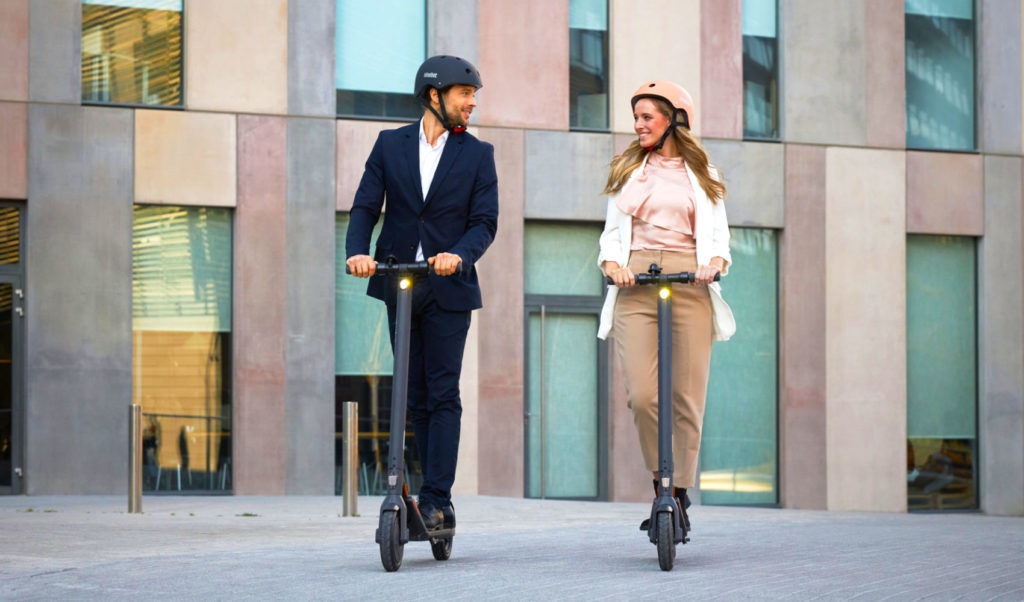 A man and woman riding their electric scooters to work
