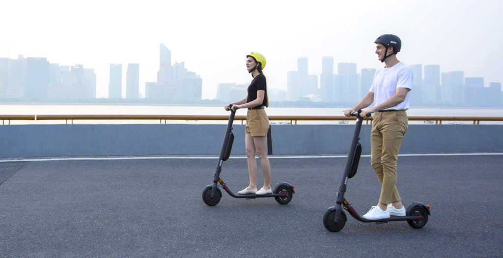 Two people riding their electric scooters on a bridge