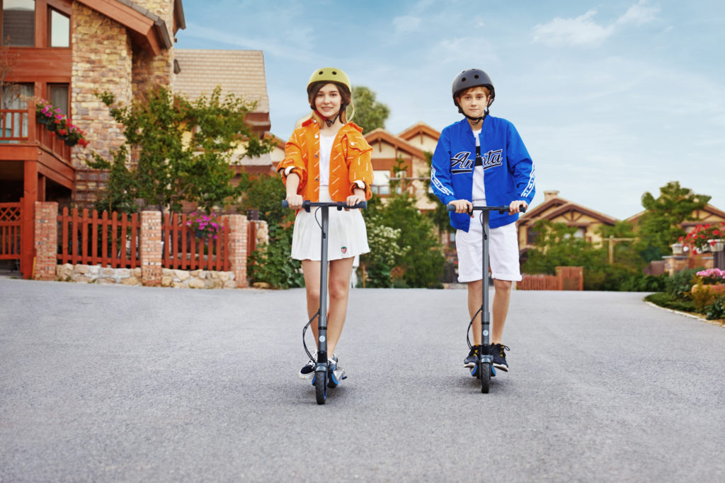 Two teens riding on their electric scooters