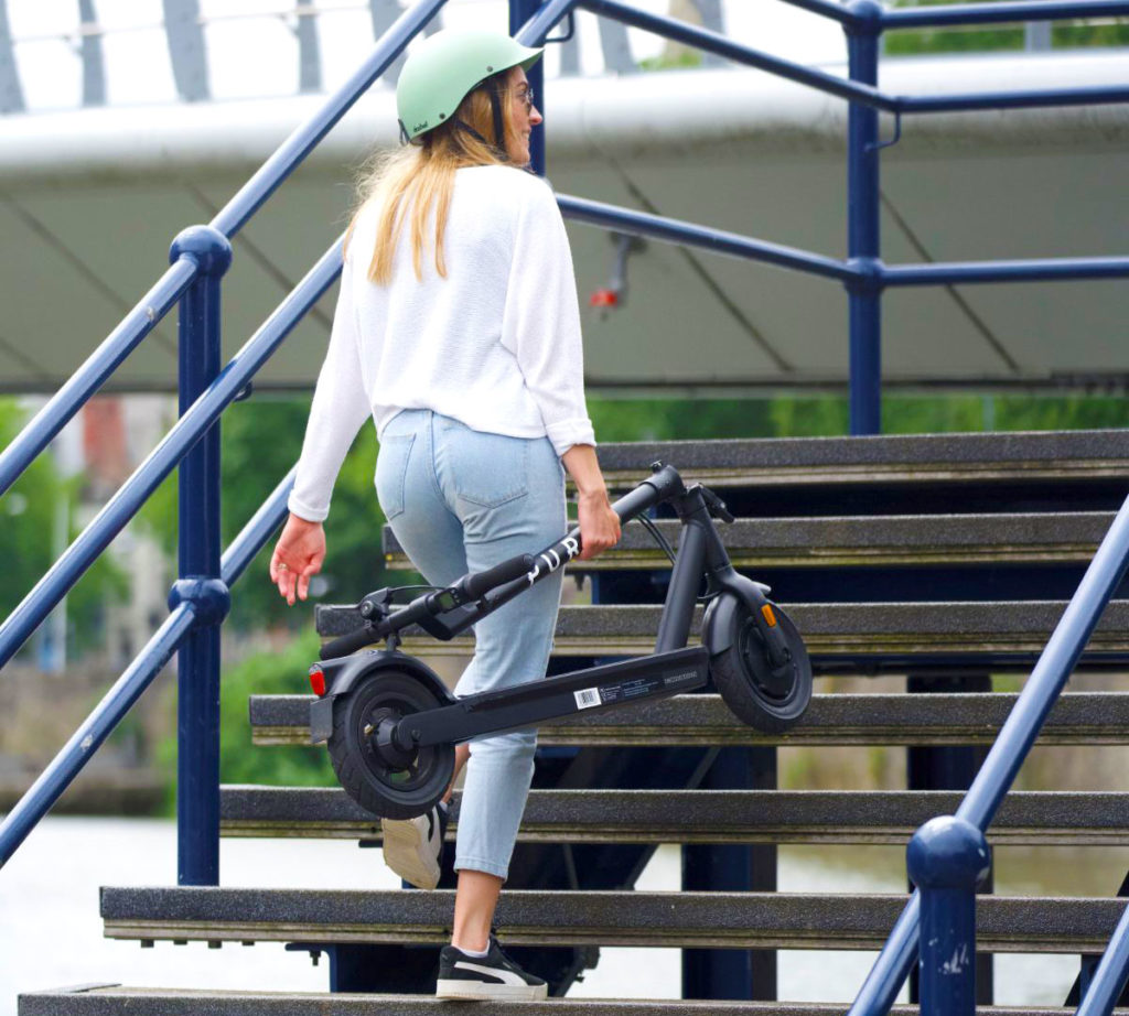 A lady carrying a folded Pure Air e-scooter up some stairs.