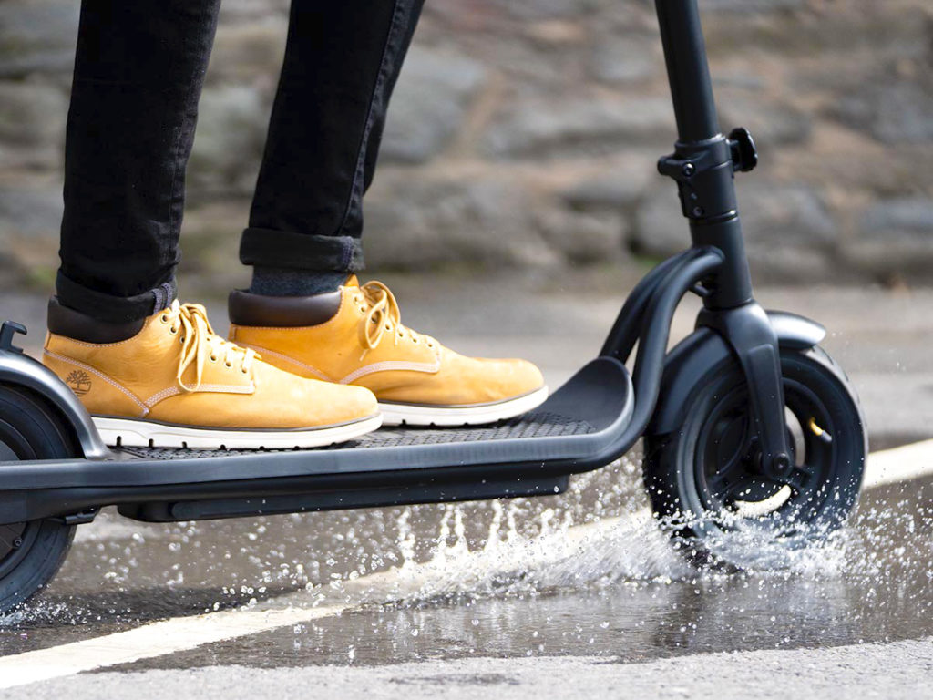 A picture of a person riding the Pure Air e-scooter through a puddle of water