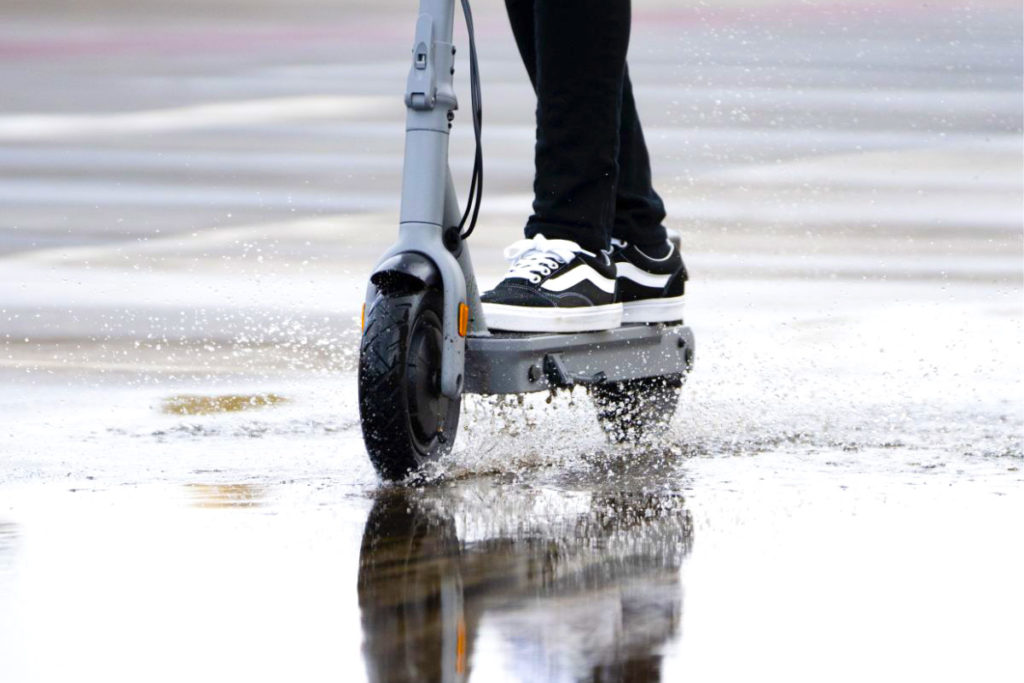 A pure Air Pro e-scooter being ridden in the rain.