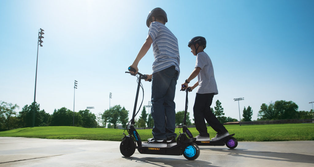 two kids riding their e-scooter at the sports fields
