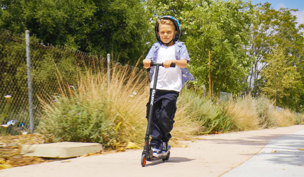 A picture of a child riding on his Razor Turbo A Black Label electric scooter