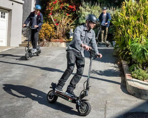 three prople riding their electric scooters