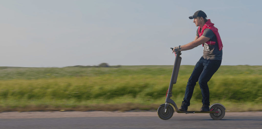 A man riding his Turboant X7 Pro electric scooter along the road.