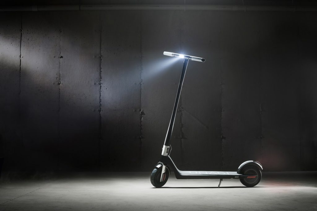 A photo of the Unagi Model One E500 electric scooter with its lights on