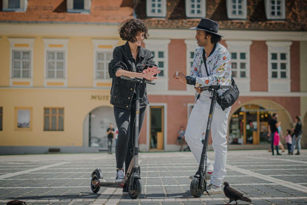 Two people standing on their Electric Scooters